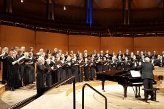 KölnChor singt auf der Bühne der Kölner Philharmonie, dirigiert von Wolfgang Siegenbrink