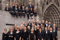 KölnChor steht und sitzt vorm Portal des Kölner Doms