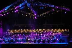 KölnChor steht auf bunt angeleuchteter Showbühne mit Orchester
