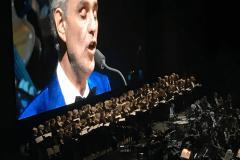 KölnChor steht mit Orchester auf der Bühne der Lanxess Arena vor Andrea Bocelli Screen