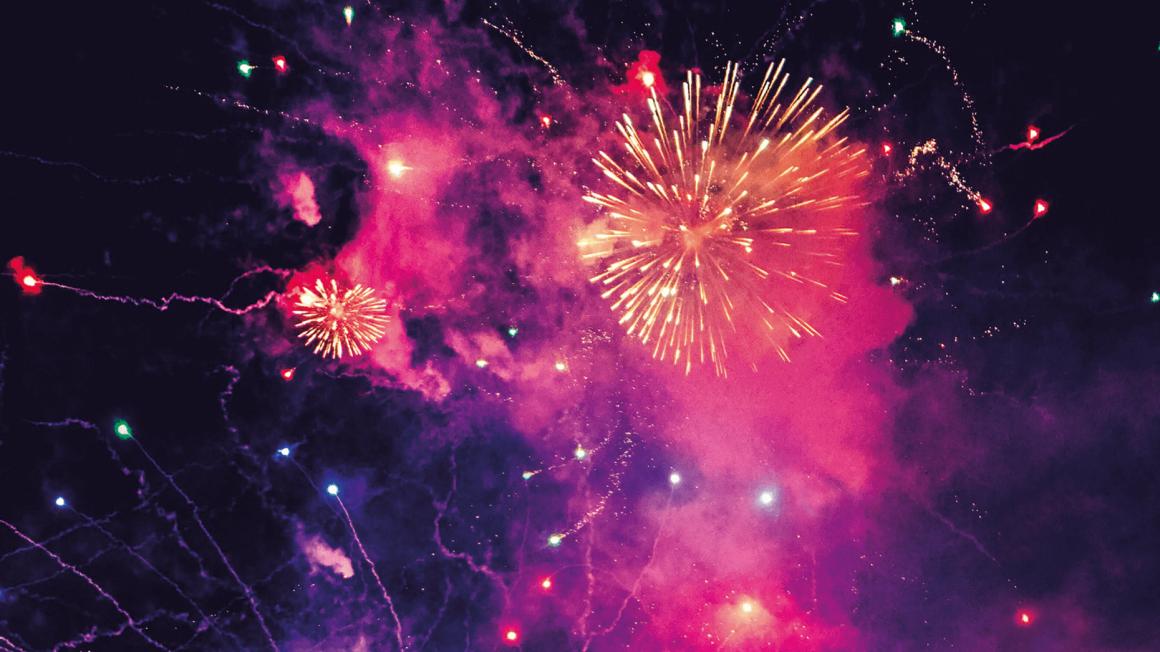 Pink-violett-gelbes Neujahrsfeuerwerk vor schwarzen Himmel