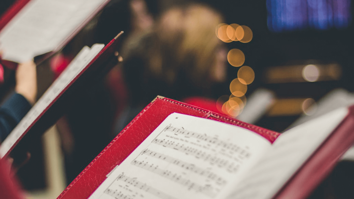 Aufgeschlagene Noten in rotem Umschlag in weihnachtlich beleuchteter Kirche