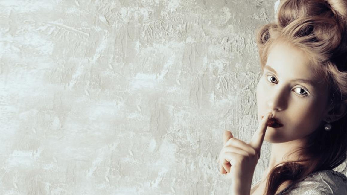 Historisch gekleidete Frau hält Finger vor die Lippen