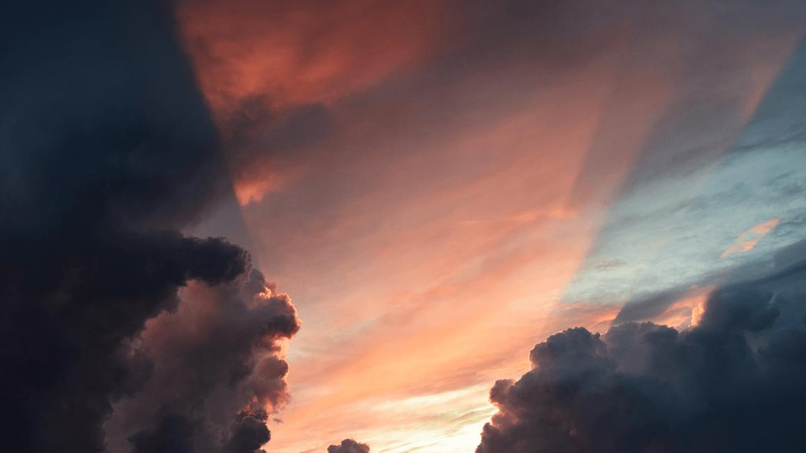 Sonnenuntergang mit rosa Sonnenstrahlen hinter dunklen Wolken
