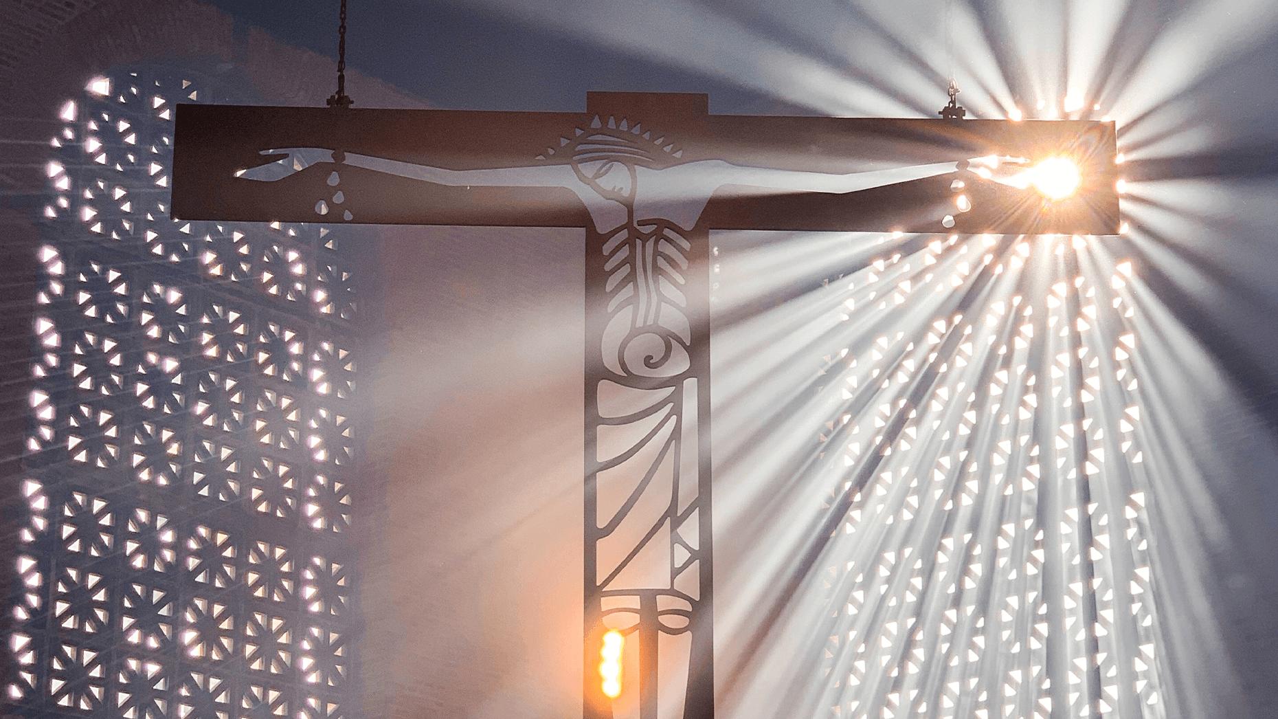Sonnenstrahlen hinter Jesus-Kreuz in Kirchen-Altarraum