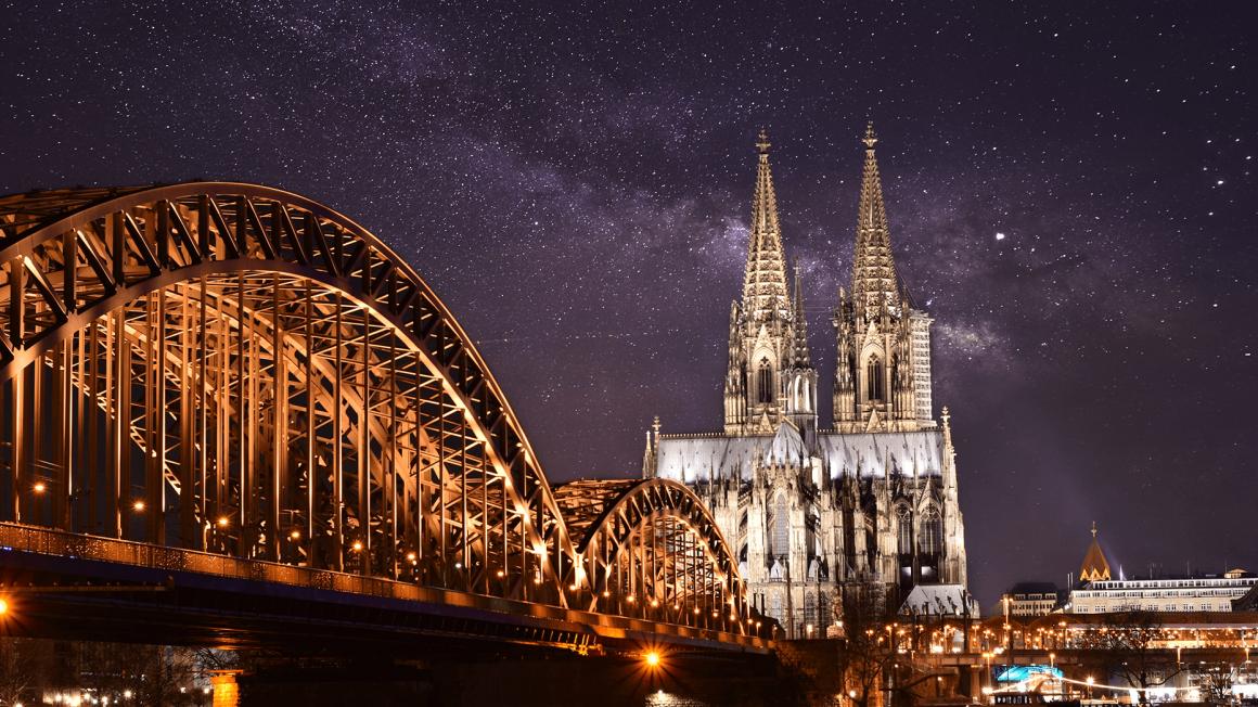 Kölner Dom und Hohenzollernbrücke angestrahlt vor Sternenhimmel