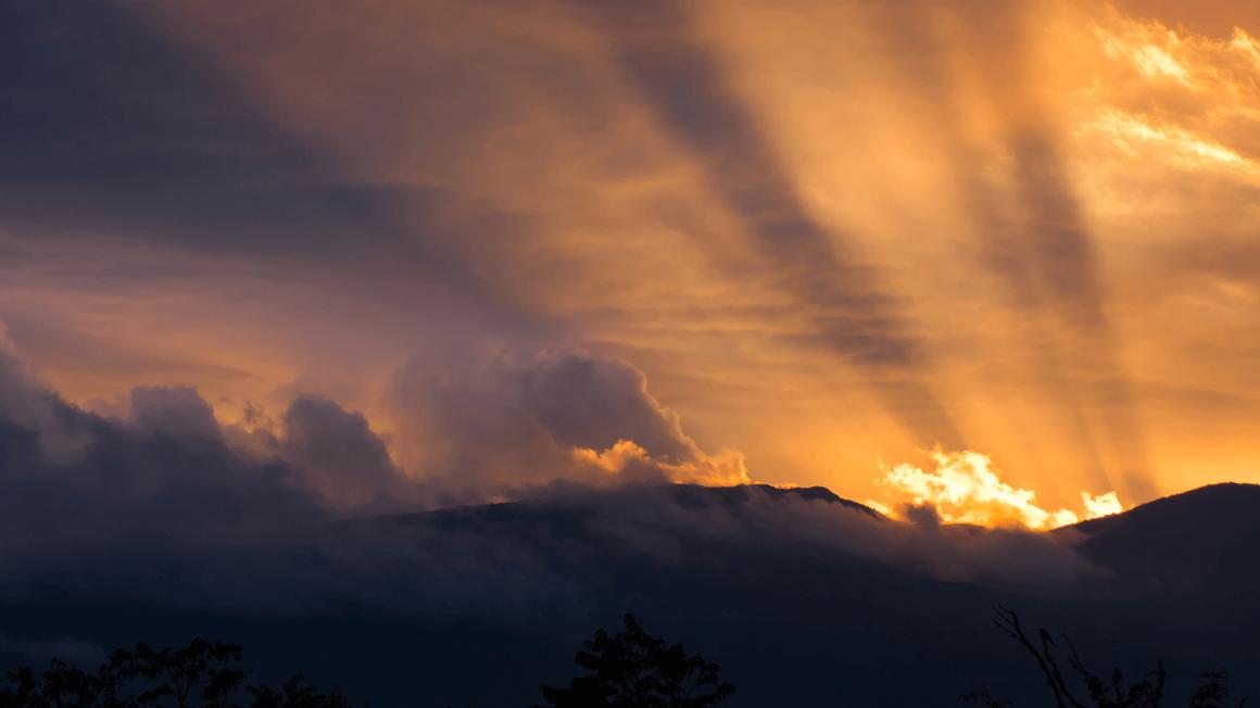 Sonnenuntergang mit gelb-leuchtenden Sonnenstrahlen hinter Berg