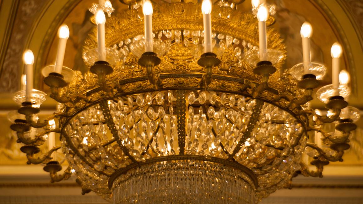 Prunkvoller goldener Kronleuchter in einem Opern-Treppenhaus