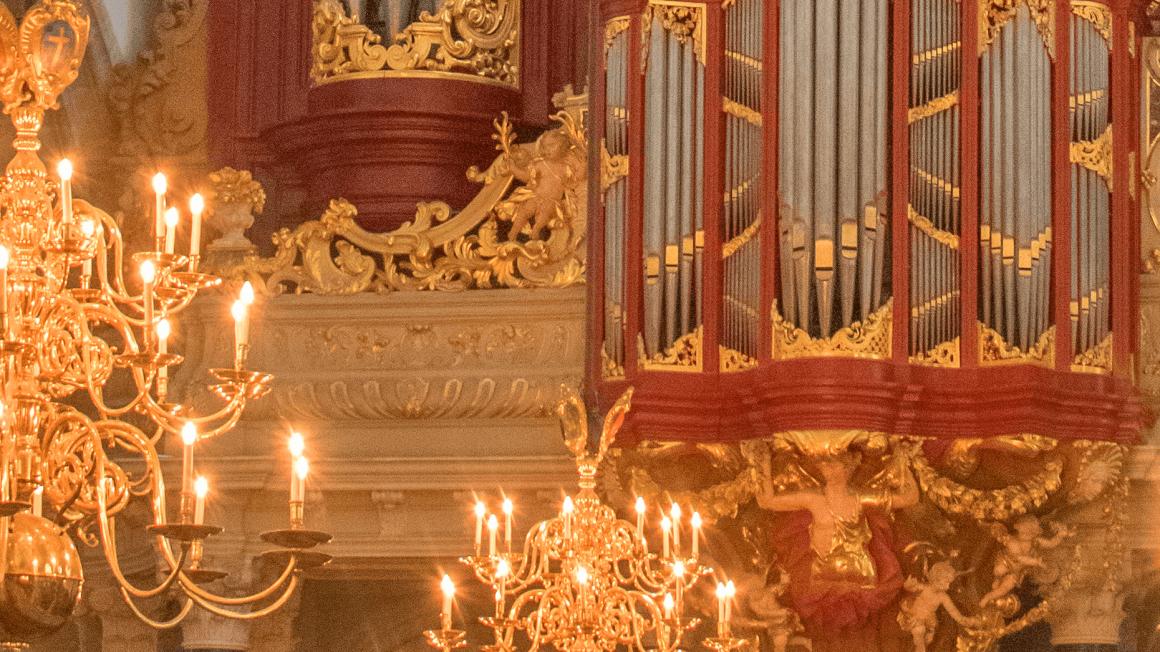 Rot-goldene Orgel mit brennendem Kronleuchter davor