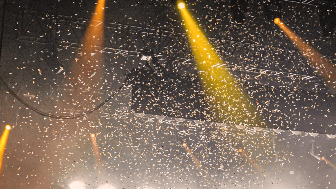 Orange und gelbe Scheinwerfer und Konfetti über Bühne