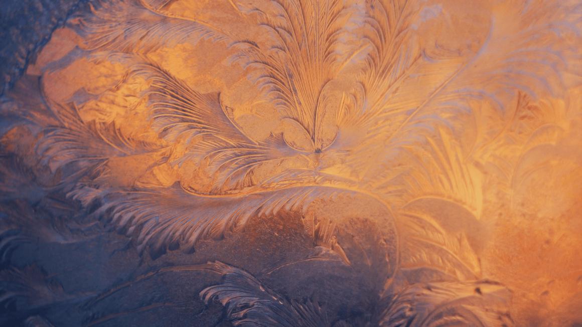 Eiskristalle von hinten dunkelblau und gelb-orange angeleuchtet